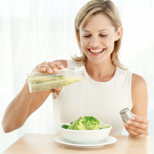 portrait of a woman pouring dressing on a bowl of salad : Stock Photo