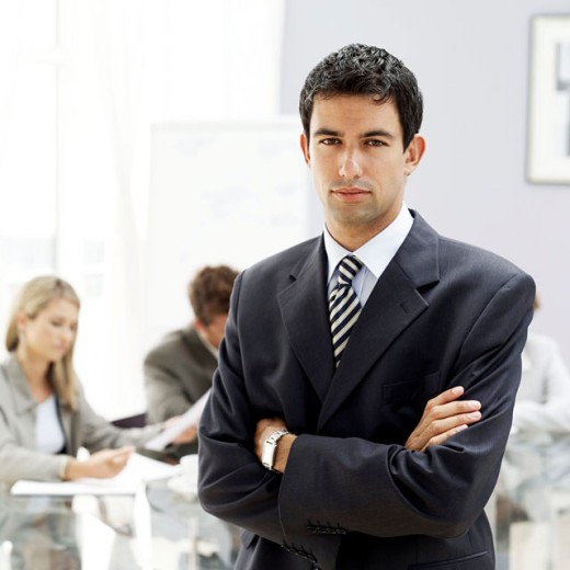 portrait of a young businessman with arms folded standing in a meeting room : Stock Photo