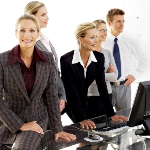 Stock Photo: 1491R-983770 portrait of a young woman standing with colleagues at a work station