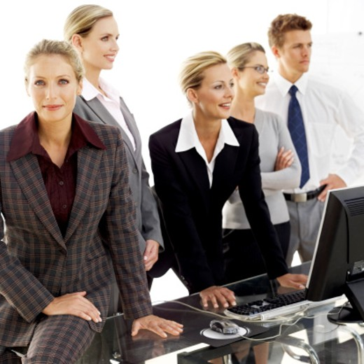 Stock Photo: 1491R-983870 portrait of a young woman standing with colleagues at a work station