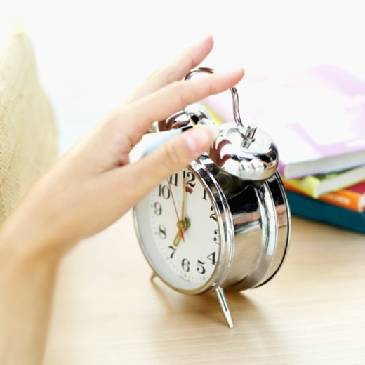 Close-up of a woman's hand on alarm clock : Stock Photo