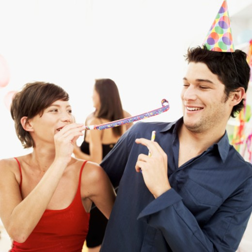 woman blowing a party blower at a man : Stock Photo