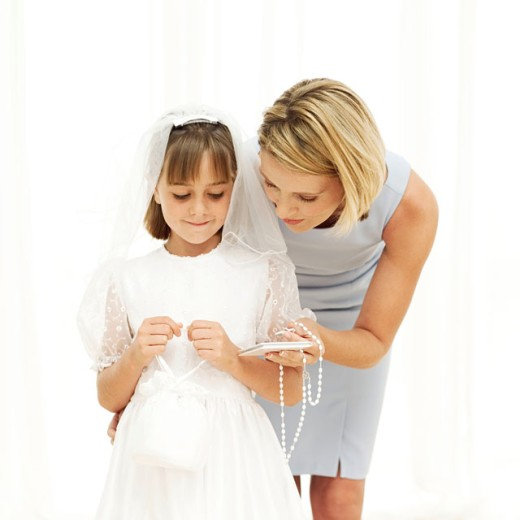 Stock Photo: 1491R-984749 Young woman giving a rosary bead and prayer book to a girl (11-13) wearing her first holy communion dress
