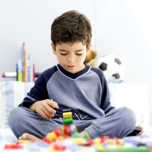portrait of a young boy playing with building blocks : Stock Photo