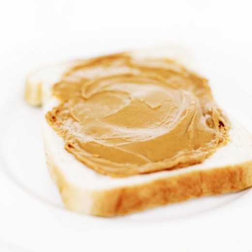 Stock Photo: 1491R-986354 close-up of peanut butter spread on a slice of white bread