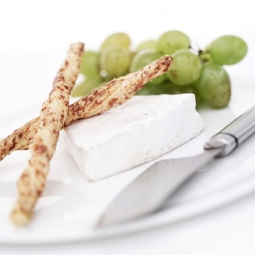 close-up of bread sticks and a slice of cottage cheese on a plate : Stock Photo