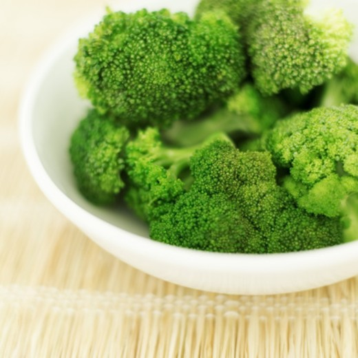 close-up of a bowl of cut pieces of broccoli : Stock Photo