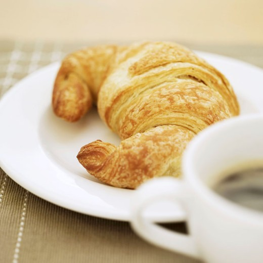 close-up of a cup of hot black coffee and a croissant : Stock Photo