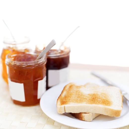 close-up of assorted jams in bottles and two slices of toast on a plate : Stock Photo