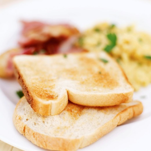 close-up of toast served with scrambled eggs and bacon (selective focus) : Stock Photo