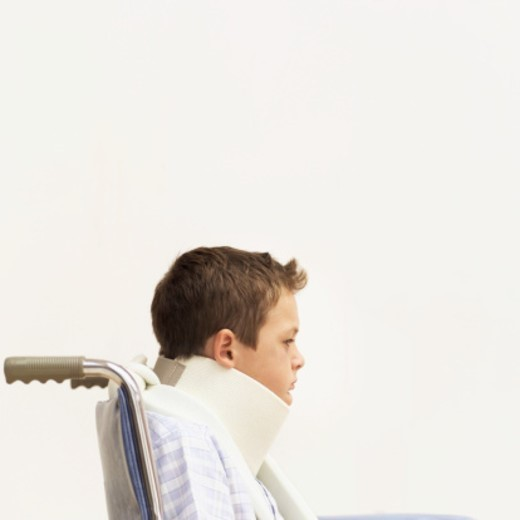 Stock Photo: 1491R-989046 Close-up of a young boy (8-10) in a wheelchair wearing a neck brace