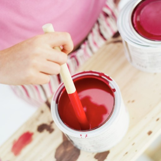 close-up of a hand mixing a bowl of red paint : Stock Photo