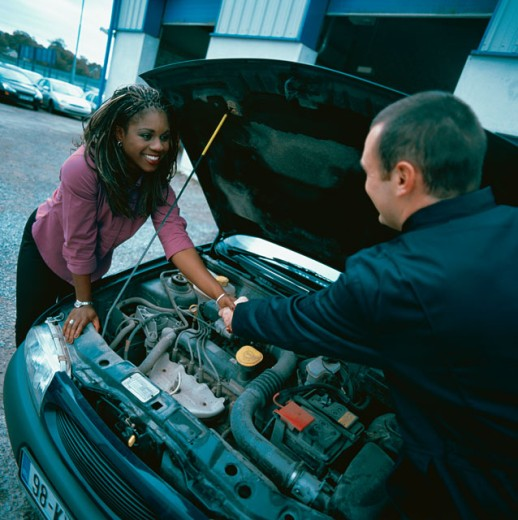 Woman shaking hands with a car salesman over a car engine : Stock Photo