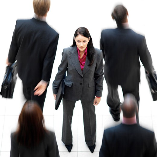 Elevated view of a young businesswoman standing among executives walking by : Stock Photo
