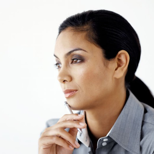 Young businesswoman sitting with a pen against her chin : Stock Photo