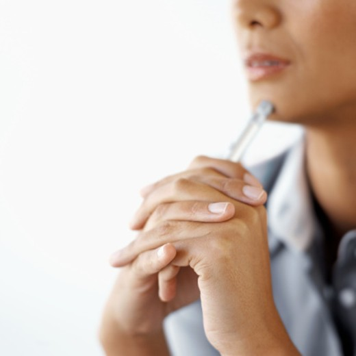 Close-up of a young businesswoman holding a pen against her chin : Stock Photo