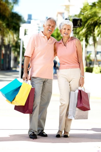 Portrait of an elderly couple carrying shopping bags : Stock Photo