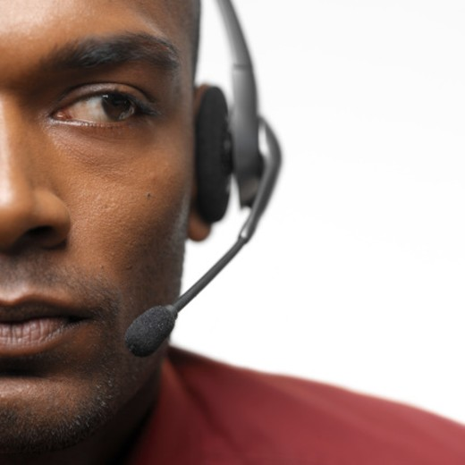 Close-up of a young businessman wearing a telephone headset : Stock Photo