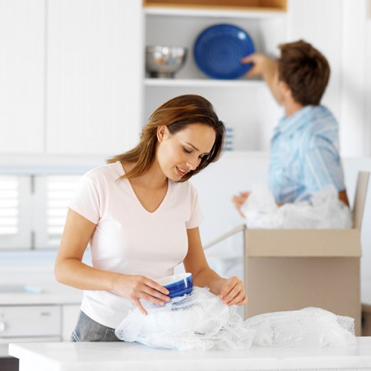Young couple unpacking crockery from a cardboard box : Stock Photo