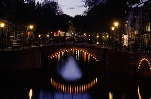 Stock Photo: 1495-497 Electric lights reflected in a canal, Amsterdam, Netherlands