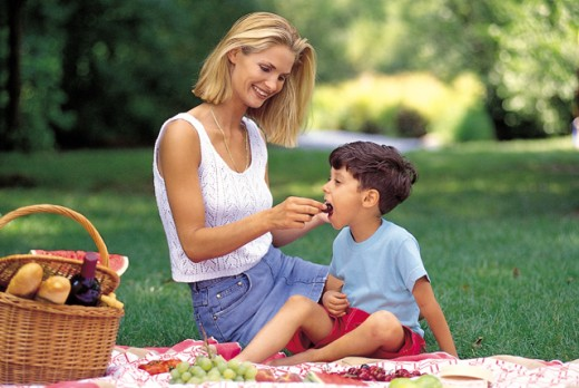 Side profile of a mother feeding her son in a park : Stock Photo