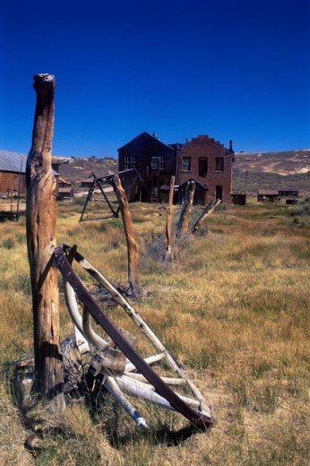 Stock Photo: 1505-120 Old wagon wheel lying against a wooden pole in front of a house, Bodie State Historic Park, California, USA