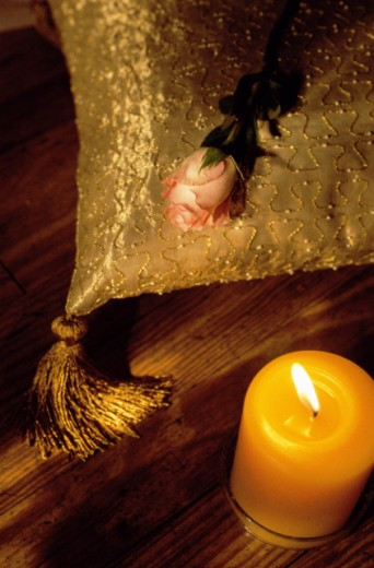 High angle view of a candle with a rose and cushion : Stock Photo