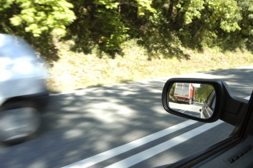 Reflection of a truck in the side view mirror of a car : Stock Photo