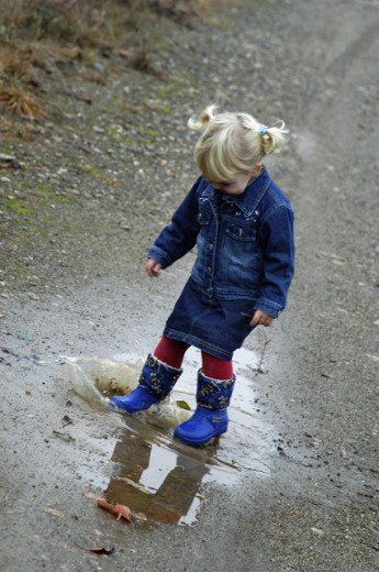 Stock Photo: 1517-344 High angle view of a girl splashing in a puddle