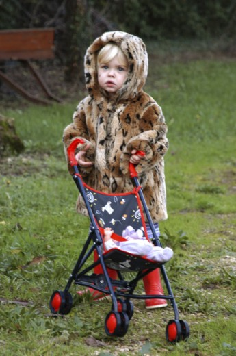 Stock Photo: 1517-717 Portrait of a girl standing on a lawn with a baby stroller