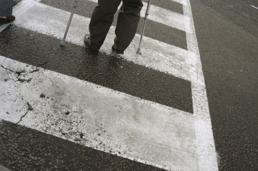 Low section view of a man on crutches crossing at a zebra crossing : Stock Photo