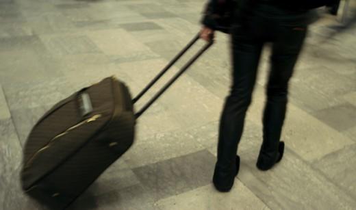 Low section view of a woman walking with her luggage : Stock Photo