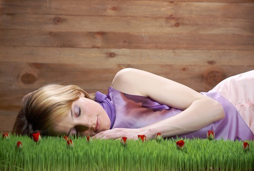 Young woman sleeping on grass : Stock Photo