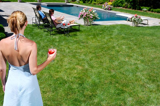 Stock Photo: 1522-289A Rear view of a young woman holding a drink and a young couple sitting at poolside