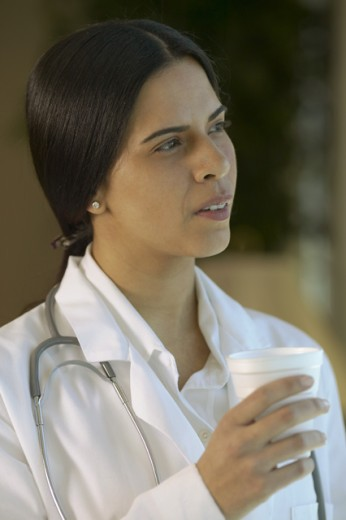 Stock Photo: 1523R-206A Side profile of a female doctor holding a cup