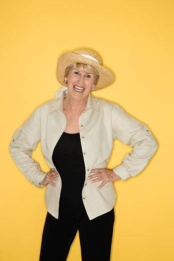 Caucasian mature adult female with hands on hips smiling. : Stock Photo