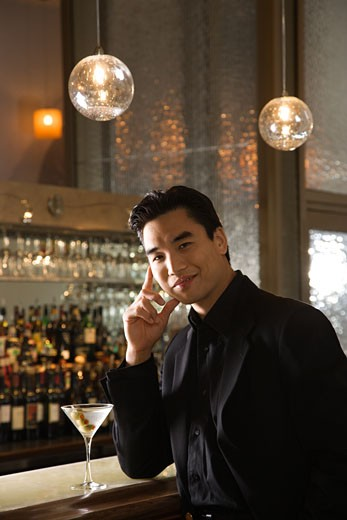 Prime adult Asian male standing at bar with cocktail. : Stock Photo