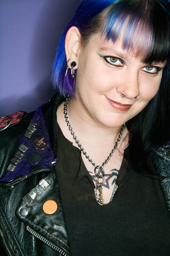 Portrait of Caucasian woman with blue hair and black leather jacket against blue background. : Stock Photo