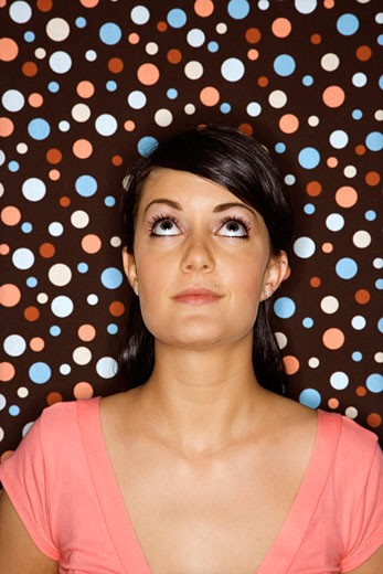 Stock Photo: 1525R-100883 Young adult female Caucasian looking up on polka dot background.