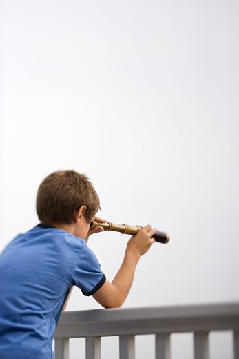 Caucasian pre-teen boy leaning on railing looking through telescope. : Stock Photo