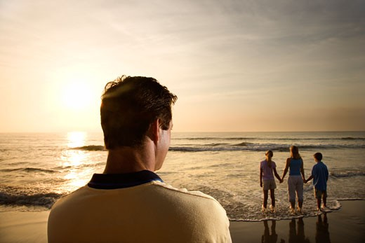 Caucasian mid-adult man standing and watching mid-adult woman with children on beach. : Stock Photo