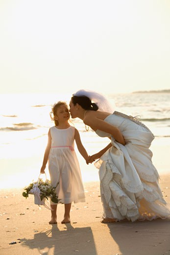 Caucasian mid-adult bride kneeling to give flower girl a kiss on the cheek while holding hands barefoot on beach. : Stock Photo