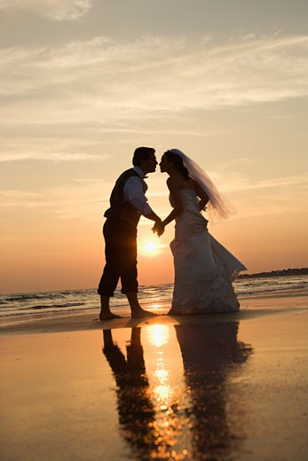 Stock Photo: 1525R-101746 Caucasian prime adult male groom and female bride holding hands and kissing barefoot on beach at sunset.