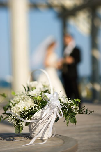 Flower basket with Caucasian bride and groom blurred in background. : Stock Photo