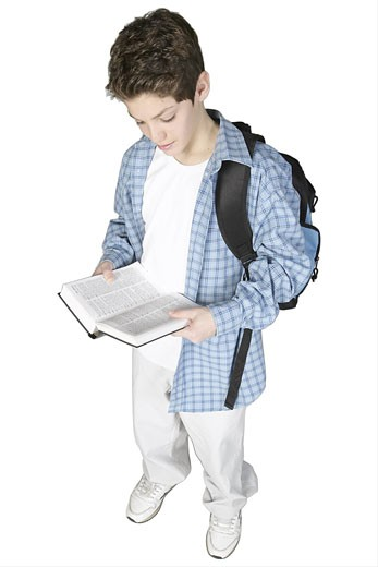 Teenaged boy carrying book bag and reading book : Stock Photo