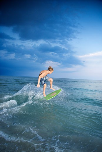 Caucasian male teen riding skimboard. : Stock Photo