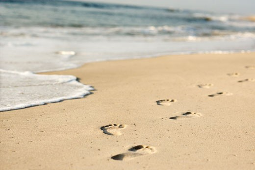 Stock Photo: 1525R-101960 Scenic sandy coastline with footprints and waves.