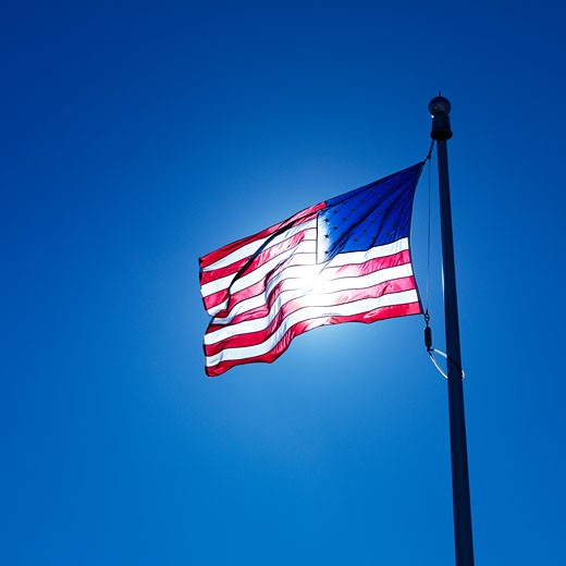 Stock Photo: 1525R-102660 American flag on flagpole waving against blue sky with sun shining through from behind.