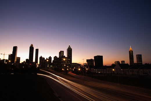 Stock Photo: 1525R-102763 Nightscape of Atlanta, Georgia skyline with blurred automobile lights on highway.