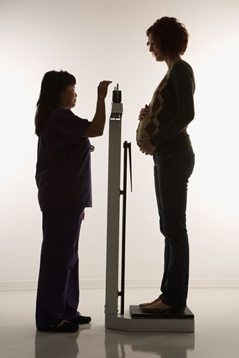 Pregnant Caucasian mid-adult woman being weighed by nurse. : Stock Photo